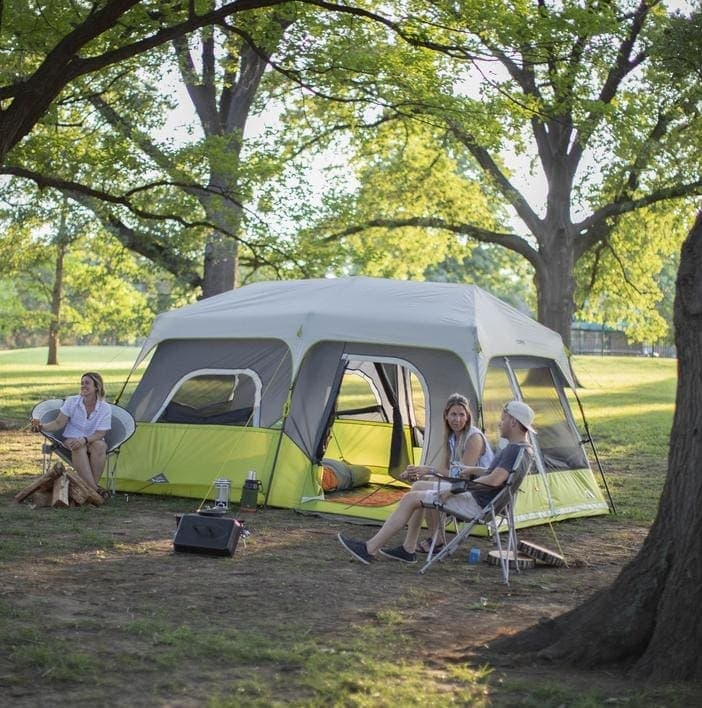 People conversing outside a Core Instant Cabin Tent