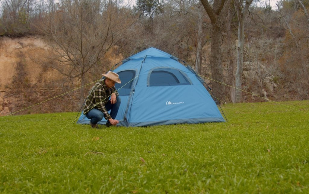 A man setting up a Moon Lence Pop Up Family Tent