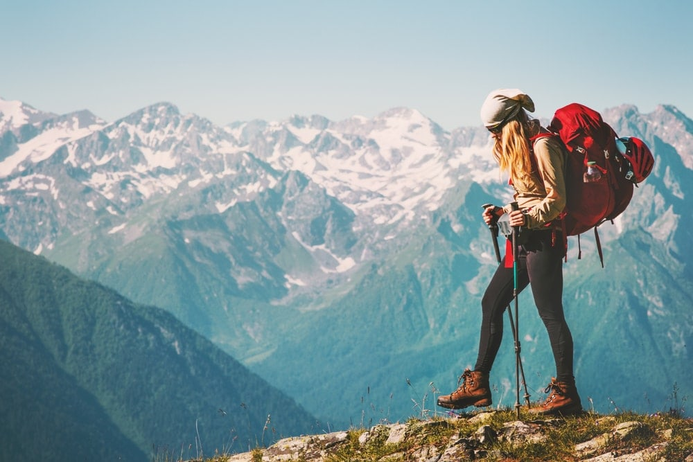 A woman hiking with a red backpack