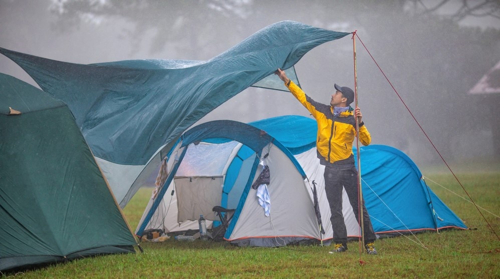A man setting up a camping tarp and tent during a bad weather