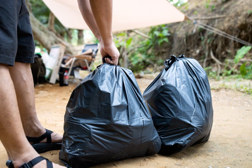 Man holding a plastic trash bag