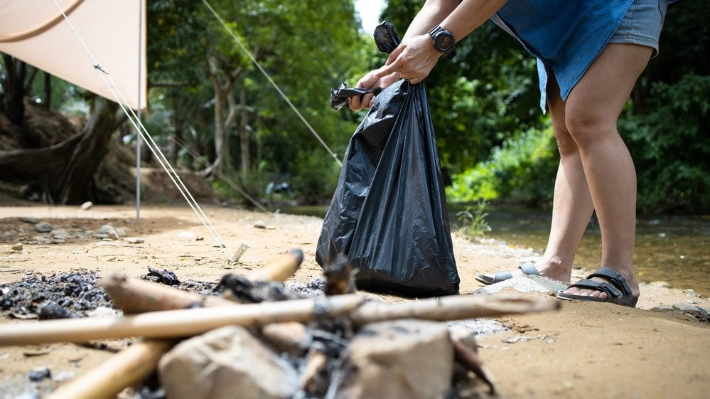 A woman holding a plastic trash bag in campground