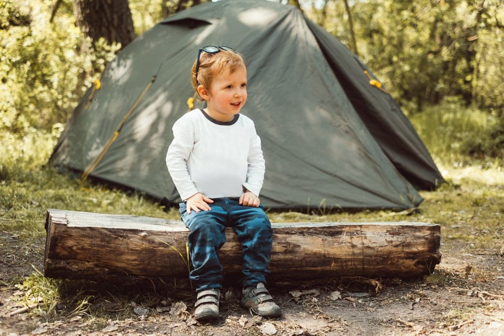A child sitting on tree trunk with a tent behind