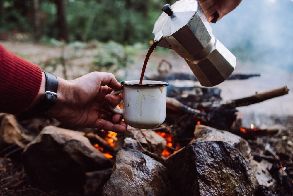 Pouring coffee into an enamel mug