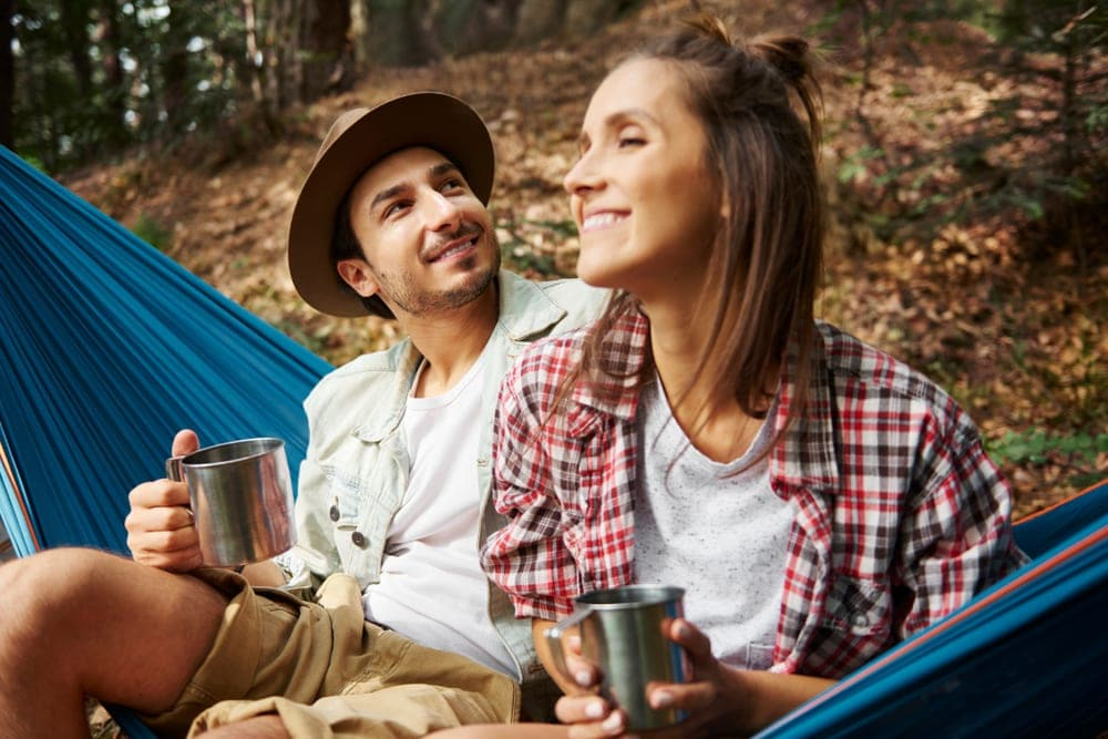 A couple sitting on a hammock in the woods