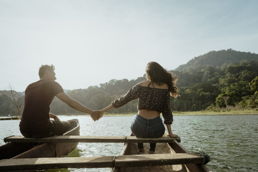 A canoe date in the lake with the couple holding hands