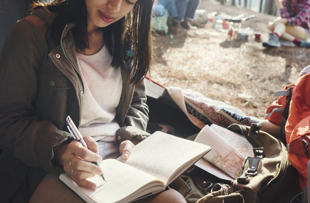 A woman writing in her journal while camping