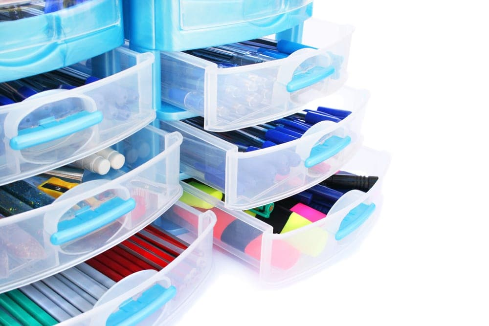 Blue plastic drawers with office supplies in it