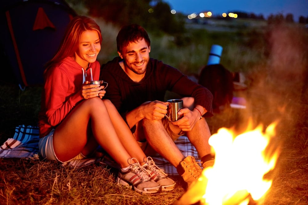 Smiling couple having a camping date