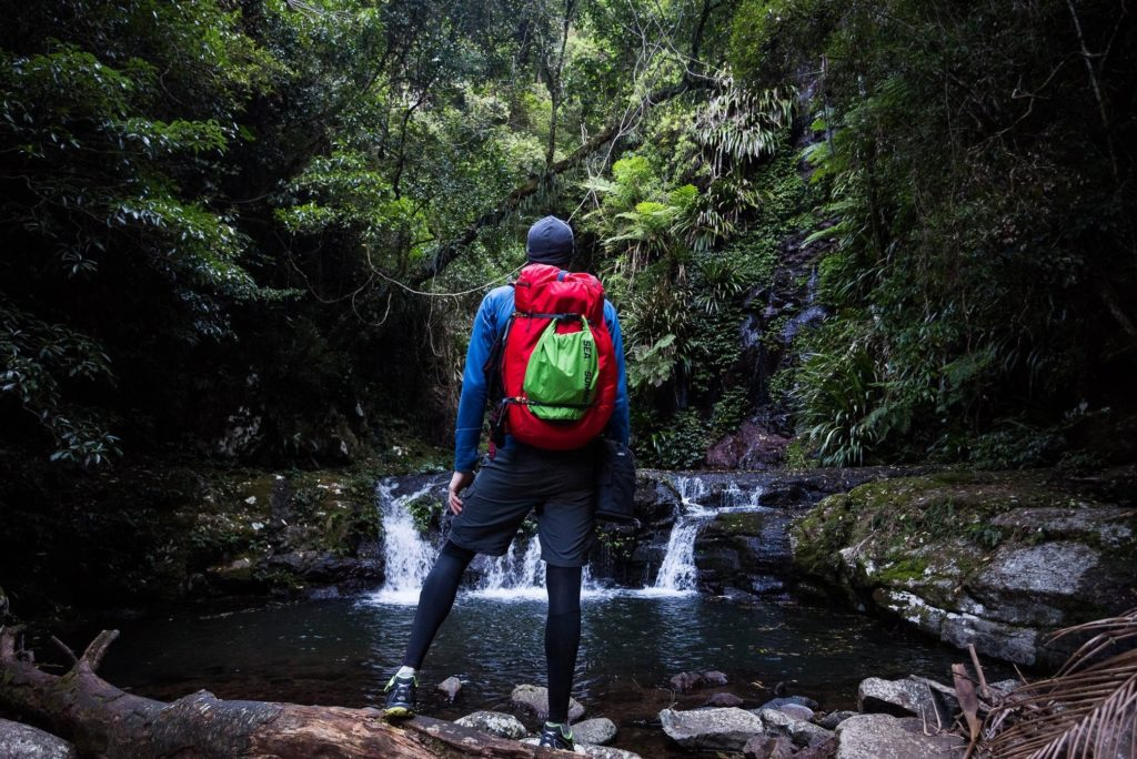 A hiker looking at a river carrying a duffle bag