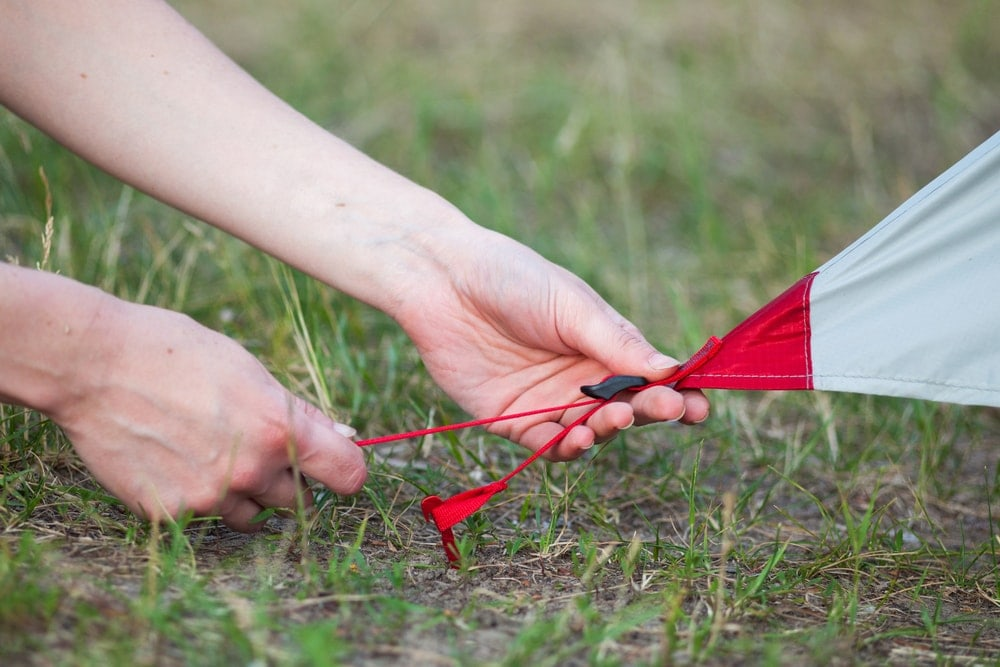 Woman setting up tent stakes
