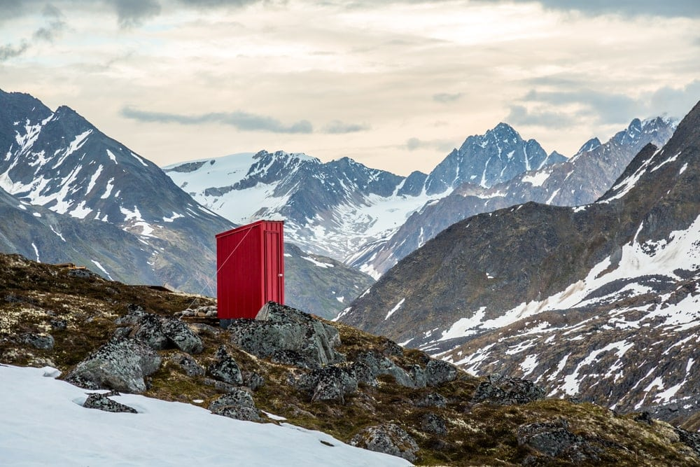 Red toilet standing in the mountains