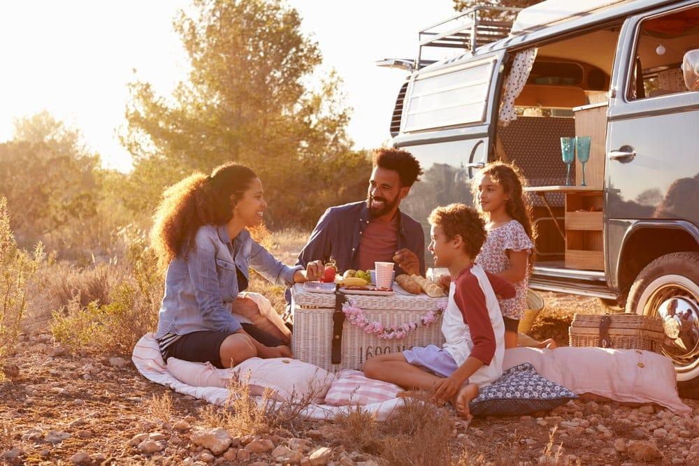 Family having picnic beside camper