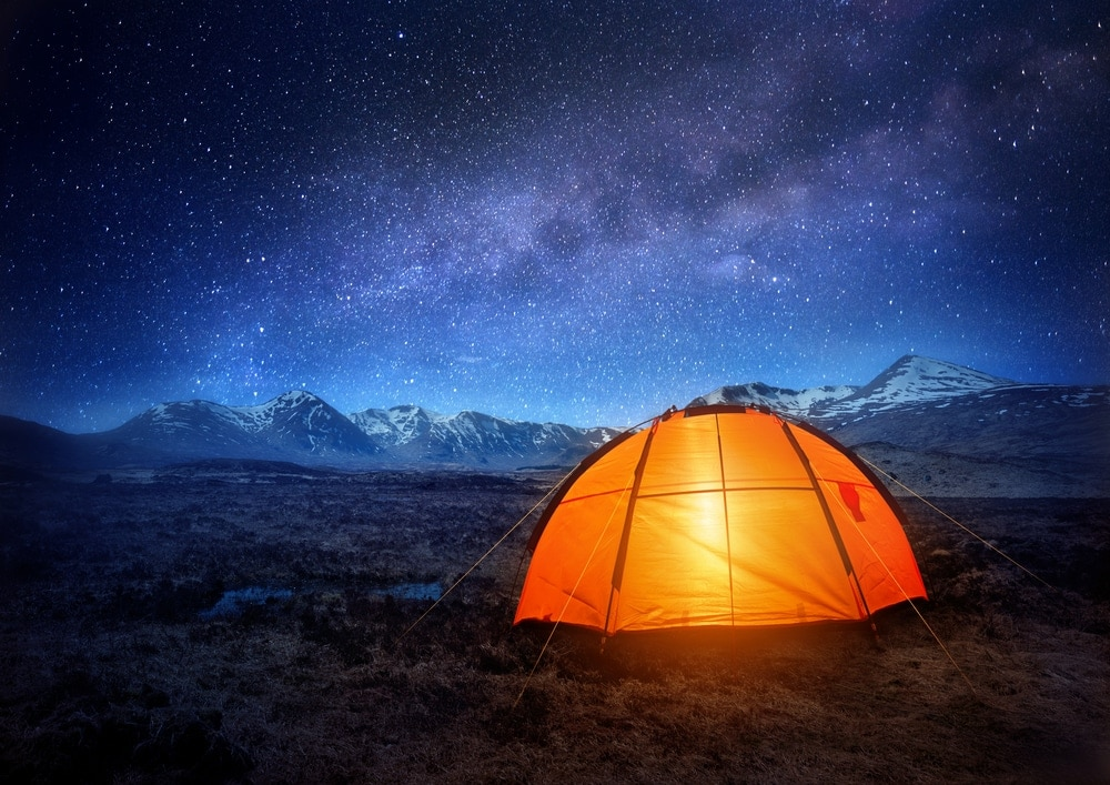 Camping Tent glowing under starry night sky