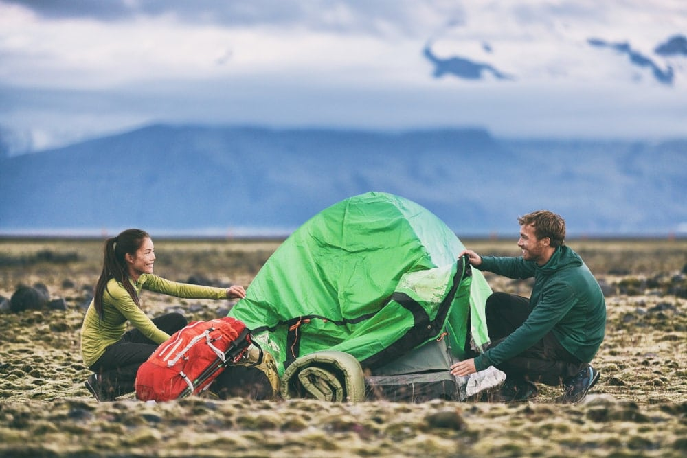 Smiling couple packing a tent