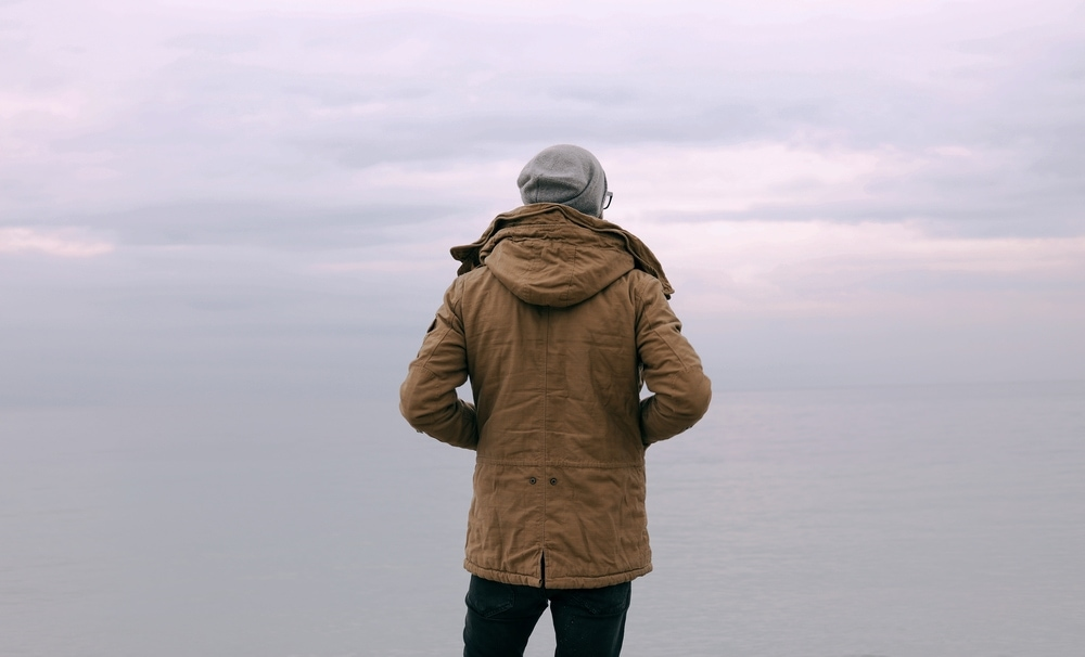 Guy in parka coat looking at horizon