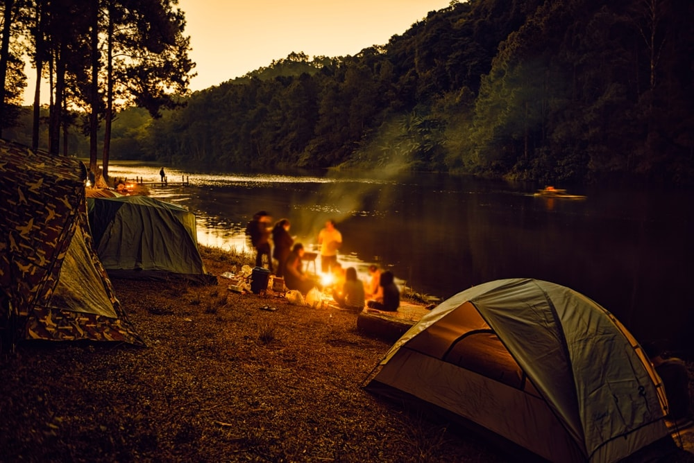 Group of people camping beside the river in twilight hour