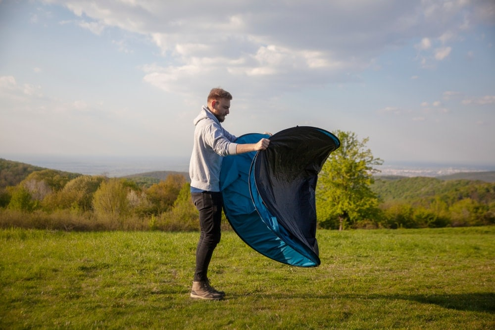 Man setting up fast pitch tent