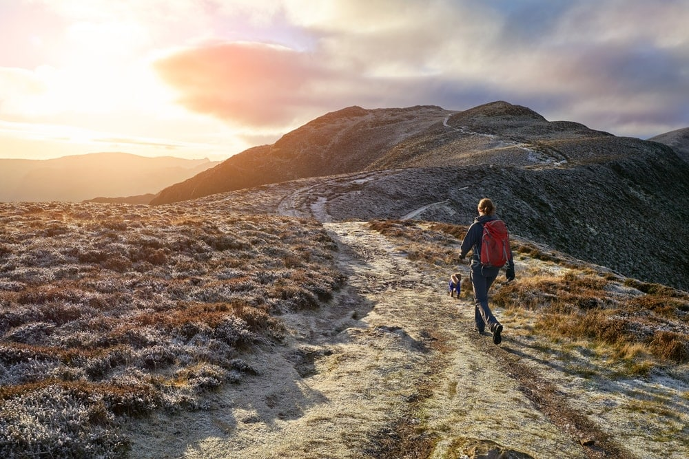 Woman and her dog walking in a fell mountainsummit
