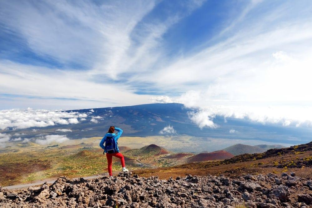 Hiker admiring the view of Mauna Loa volcano in Hawai