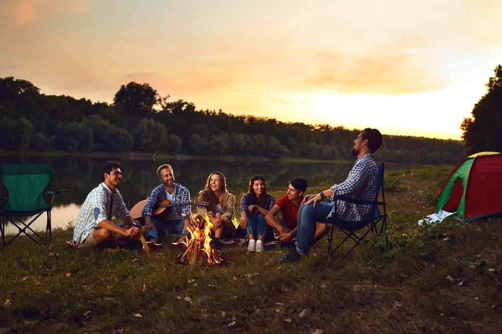Group of friends chatting and smiling with a campfire beside