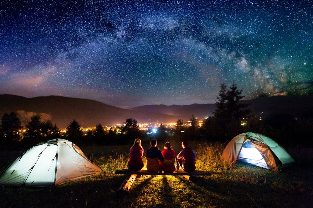 Group of friends camping under starry night with city lights view