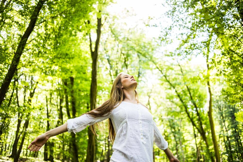 Woman enjoying sunlight in the forest