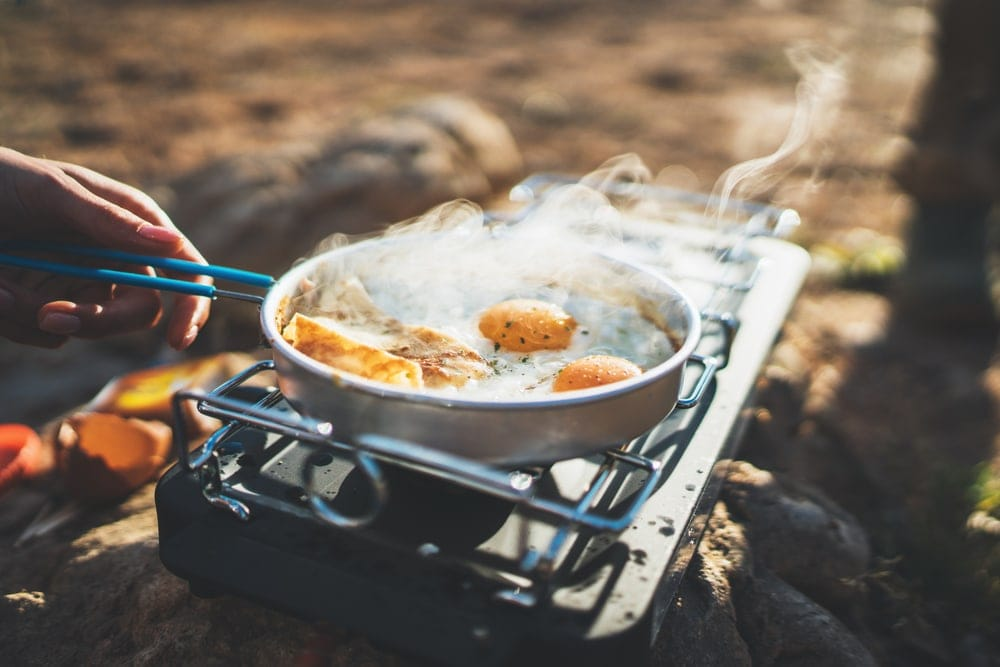 Man cooking eggs on a frying pan