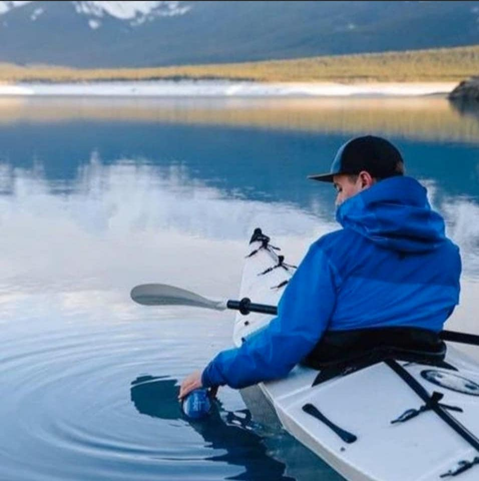 Man getting water from using a lifestraw bottle while in a kayak