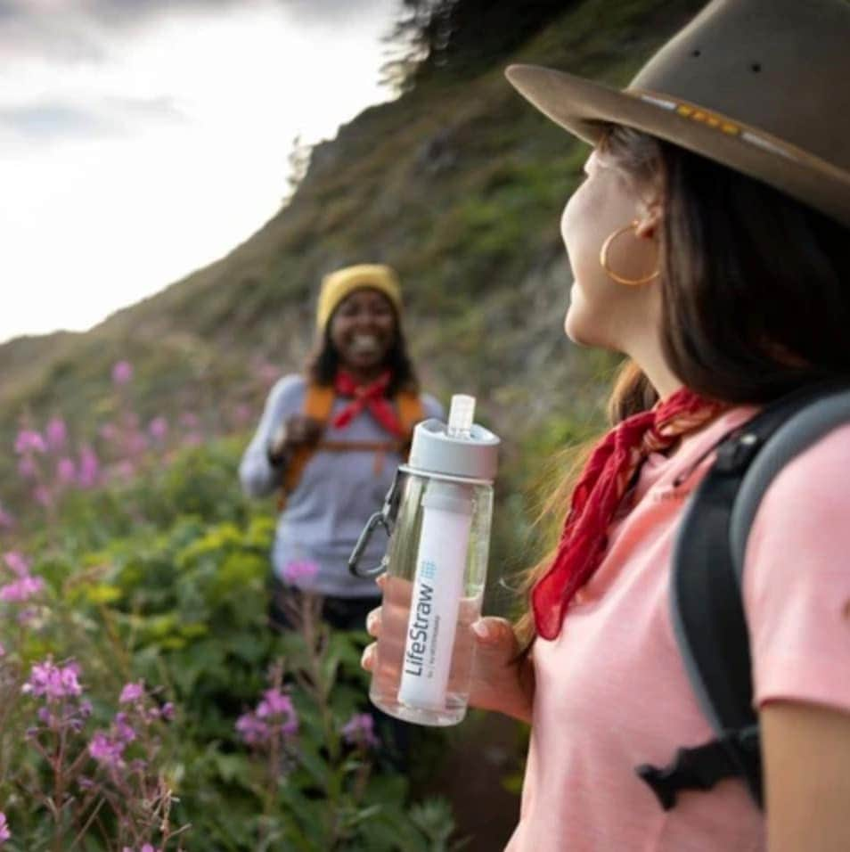 A woman holding a lifestraw bottle during a hike