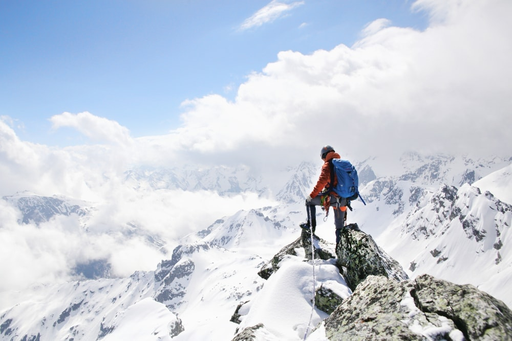Person mountaineering at the top of a mountain covered in snow