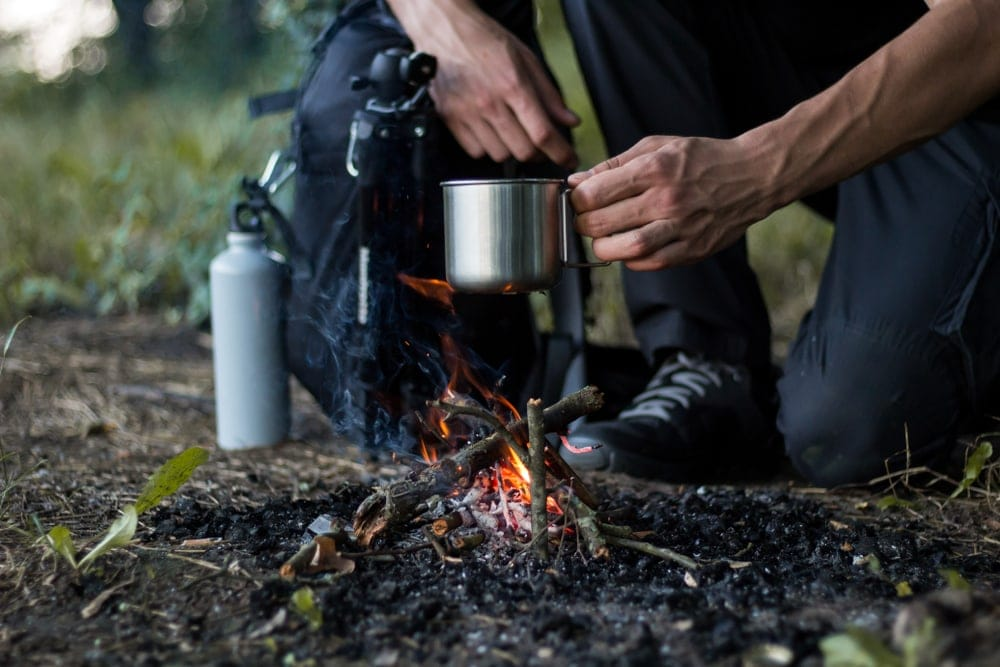 Survivalist in nature cooking on fire