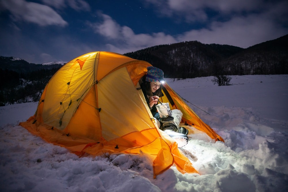 Person camping in the snow during winter camping