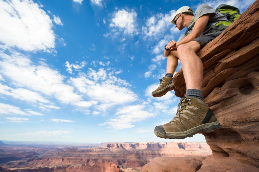 HIker wearing his hiking boots sitting at the edge of a grand canyon cliff