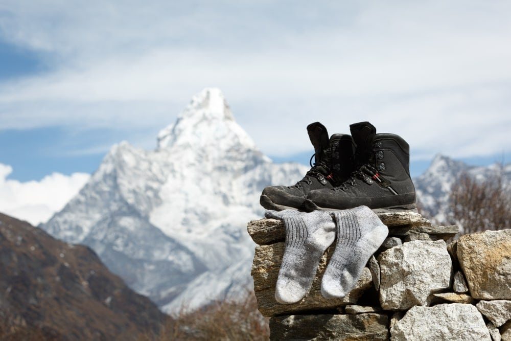 Camping boots and socks on a pile of rocks