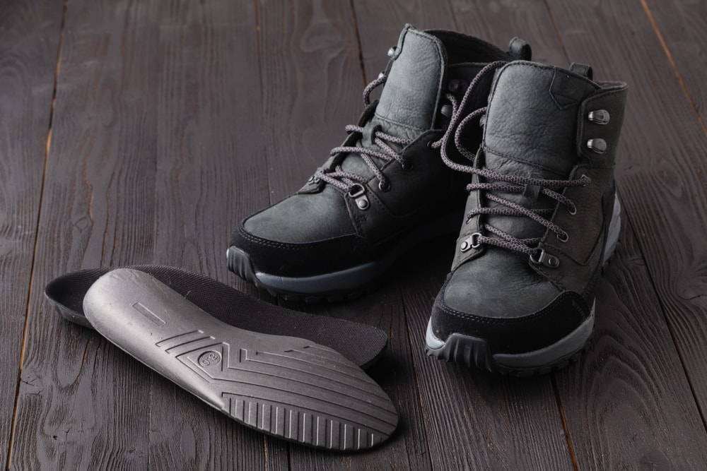 Camping boots and heated insoles on a floor