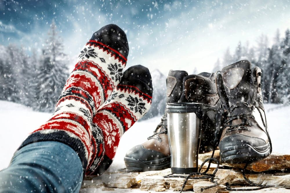 Person wearing a christmas-designed heated socks with boots and tumblr besides during winter camping