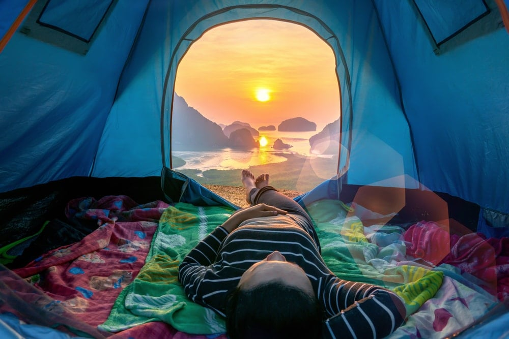 Person lying inside her camping tent