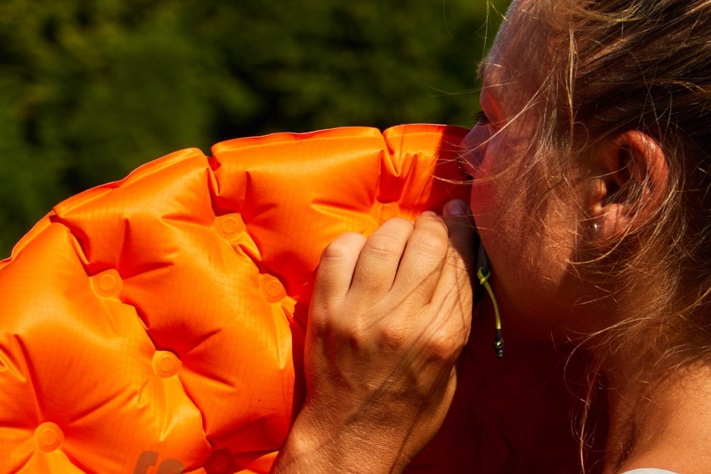 Woman inflating a sleeping bag
