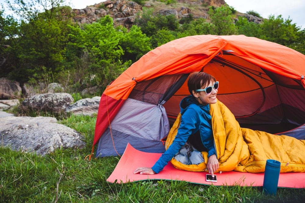 Woman wearing shades looking comfortable beside her tent