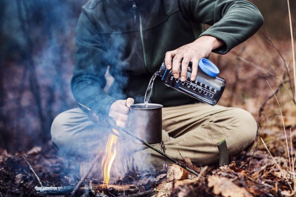 Man pouring water to a camping mug