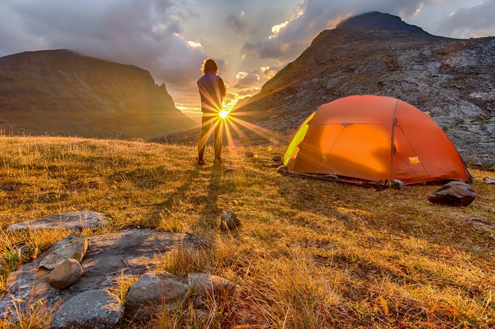 A man looking at the sun with camping tent beside