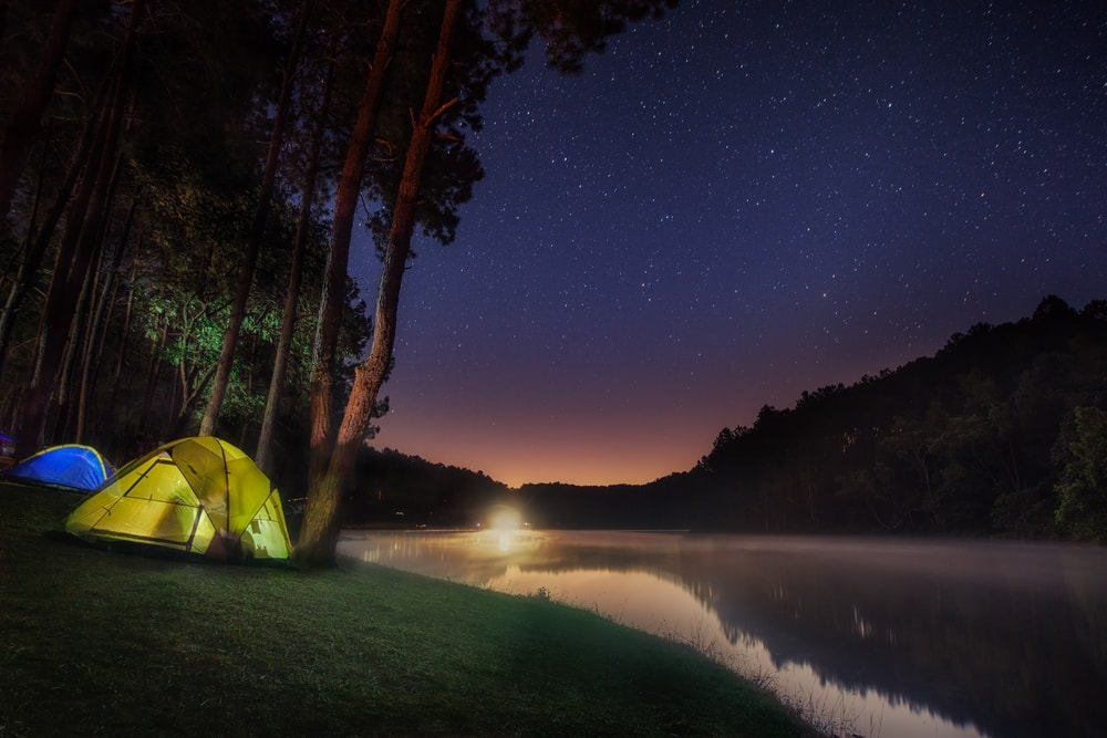 Camping tent beside lake in night time