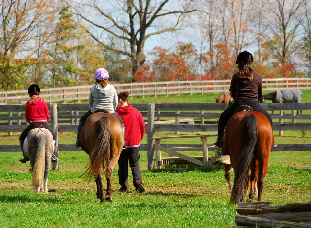Kids riding horses on a campground