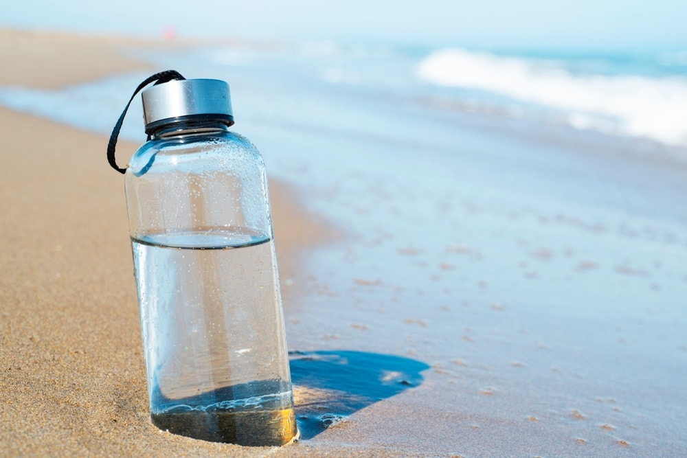 Water bottle with half part buried on the beach sand