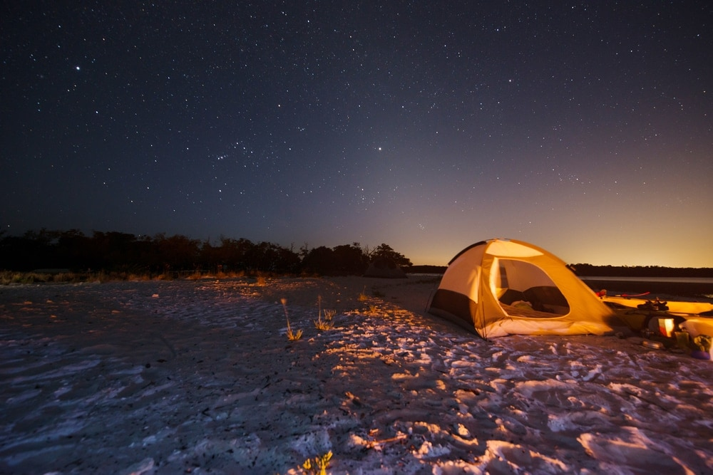 camping tent on the beach under night sky