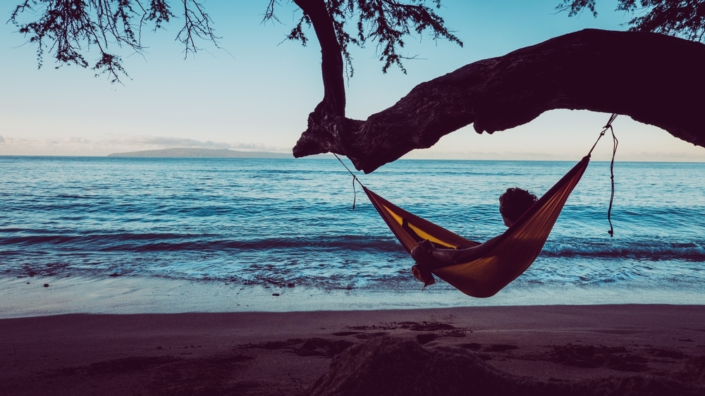 Man looking at the beach while in the hammock