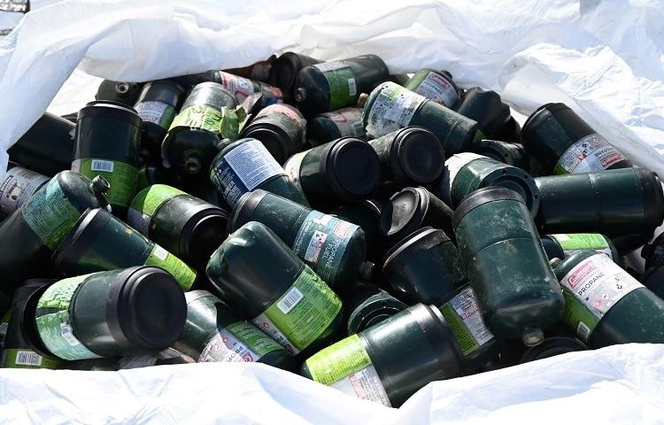 trash full of empty propane tanks