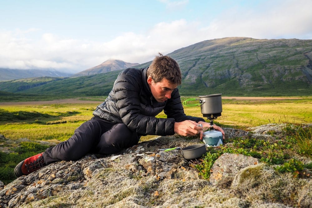 Man trying to use a canister stove to boil water while camping