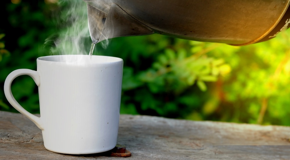 Pouring hot water to a mug from an electric kettle